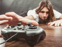 Young man with pad. Addiction and dependency concept. Young man with pad joystick playing games. Male addicted to console playstation videogames Royalty Free Stock Images