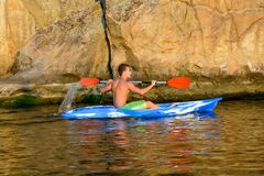 Young Man Paddling Blue Kayak on Beautiful River or Lake under High Rock in the Evening. Young Man Paddling Blue Kayak on the Beautiful River or Lake under High Royalty Free Stock Photos
