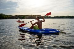 Young Man Paddling Kayak on the Beautiful River or Lake under Dramatic Evening Sky at Sunset. Young Man Paddling Kayak on the Beautiful River or Lake under the Stock Photo