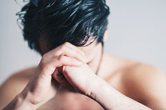 Young man in pain praying Stock Images