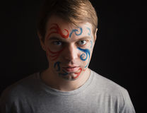Young man with paint on his face. Royalty Free Stock Photos