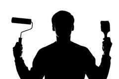 A young man with a paint roller and brush in hand Stock Photography