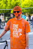 Young man painted orange at Color Run Bucharest. Young man completely covered with orange powder and violet powder on his face smiling at the Color Run event on Stock Image