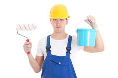 Young man painter in blue coveralls with paint brush and bucket Stock Images