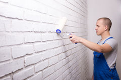 Young man painter in uniform painting brick wall with paint roll Royalty Free Stock Photo