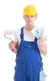 Young man painter in workwear with paintbrush and colorful palet Royalty Free Stock Photo