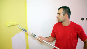 Young Man Painting Apartment. Decorator using a long roller to paint a wall in yellow Royalty Free Stock Photo