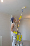 Young man painting ceiling with painting roller Royalty Free Stock Image