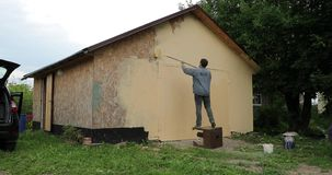 Young man painting a garage with a roller in the daytime time lapse video 4k.  stock video footage