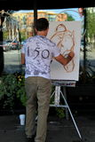 Young man painting horse and rider on busy downtown street,Saratoga,New York,2015 Royalty Free Stock Photos