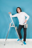 Young man painting house. Young man with paint and brushes on stepladder in interior Royalty Free Stock Photos