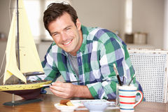 Young man painting model ship Stock Photo