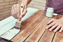 Young man painting an old wooden table. Closeup of a young caucasian man painting an old wooden table with a brush Royalty Free Stock Photos