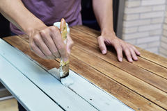Young man painting an old wooden table Stock Image