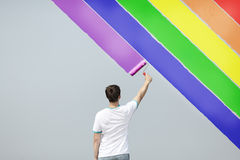 Young man painting rainbow royalty free stock image