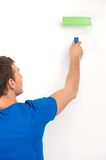 Young man painting wall in green. Royalty Free Stock Images