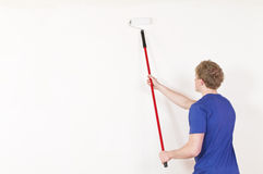 Young man painting a wall Stock Image