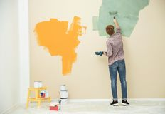 Young man painting wall indoors. Home repair. Young man painting wall indoors, space for text. Home repair royalty free stock photography