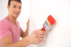 Young man painting wall and smiling. Stock Photography