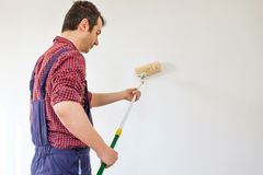 Young man painting wall with white paint and tools. One standing painter man at work with a roller painting a white wall royalty free stock photography