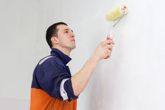 Young man is painting walls with roller Stock Photo