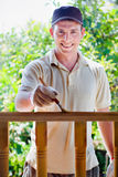 Young man painting wooden fence in the garden Stock Photography