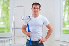 Young man with paintroller. Looking at camera Stock Photo