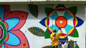 Young man paints wall in park stock video footage