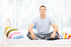 Young man in pajamas sitting on a bed Stock Images