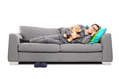 Young man in pajamas sleeping on couch with teddy bear Royalty Free Stock Photos