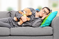 Young man in pajamas sleeping on sofa at home Stock Image