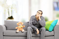 Young man in pajamas thoughts seated on sofa at home Stock Photos