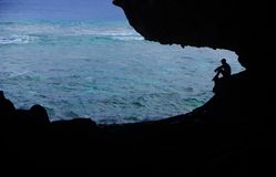 Young Man in Palaha Cave, Niue. A young man looks out over the reef from inside Palaha Cave (Niue). One of the largest coral atolls in the world, Niue is a royalty free stock photo
