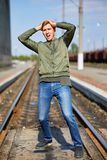 A man in a panic stands on the rails. A young man in a panic stands on the rails holding his head stock image