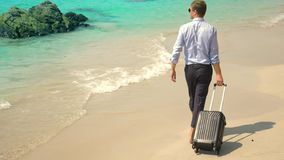 A young man in pants and a classic shirt with a suitcase walks along the beach against the backdrop of the turquoise sea royalty free stock image