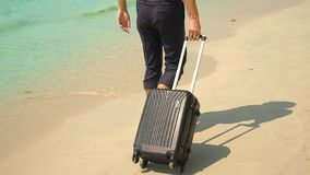 A young man in pants and a classic shirt with a suitcase walks along the beach against the backdrop of the turquoise sea stock photography