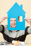 Young man with paper model of house. Royalty Free Stock Image