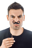 Young man with paper moustaches making faces isolated on white b Stock Photos