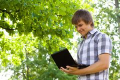 Young man in the park. Working with his laptop Stock Photos