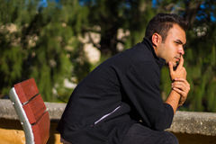 Young man on a park bench. Guy siting on a park bench with a contemplative expression in his face Royalty Free Stock Photos