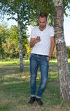 Young man in the park with cell phone Royalty Free Stock Photos