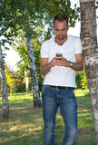 Young man in the park with cell phone Royalty Free Stock Image