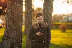 A young man in a park in a dark blue shirt. Spring. Stock Photography