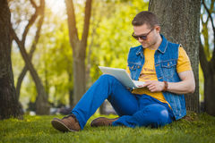 Young man in the park with laptop Royalty Free Stock Photography