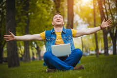 Young man in the park with a laptop Stock Image