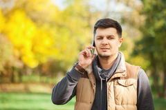 Young man in park speaking on the smartphone royalty free stock photography