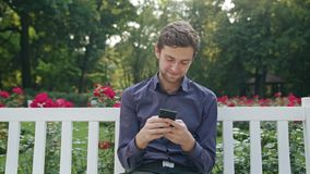 Young man in the park using a phone stock video footage