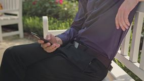 Young man in the park using a phone. A young man sitting on a white bench in the park and using a phone. Close-up shot stock video footage