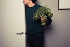 Young man with parsley is answering the door Royalty Free Stock Photos