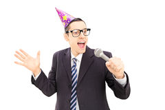 Young man with party hat singing Royalty Free Stock Image